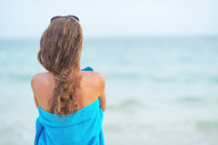Woman in towel on beach looking into distance Stock Images