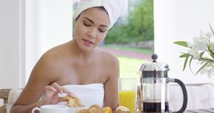 Woman in towel dipping donut in coffee stock video