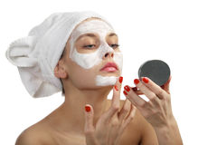 Woman in towel doing cosmetic mask Stock Image