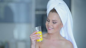 Woman in towel drinking juice Stock Photo
