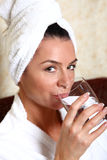 Woman in towel drinking water. Woman in white towel drinking water Stock Photography