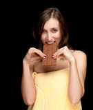 Woman in towel eating chocolate Stock Photography