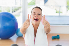 Woman with towel gesturing thumbs up in gym Royalty Free Stock Photo