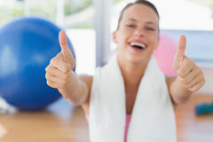 Woman with towel gesturing thumbs up in gym Royalty Free Stock Image