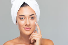 Woman with towel on head applying cream on face Stock Photo