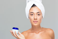 Woman with towel on head holding cream jar Royalty Free Stock Images