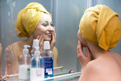 Woman with towel on head near mirror. Cheerful woman with towel on head after shower looking at her face at mirror in bathroom stock image