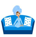 Woman with a towel on a head sits on a sofa Stock Image