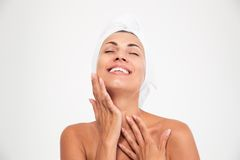 Woman with towel on head touching her fac. Spa concept. Portrait of a happy woman with towel on head touching her face isolated on a white background. Looking at Stock Photos