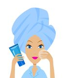 Woman with a towel on a head and tube of cream Stock Photography