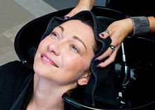 Woman with towel on her head in hair salon Stock Photo