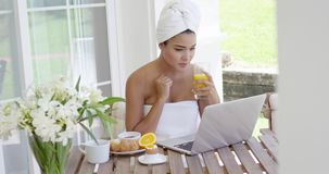 Woman in towel with laptop having breakfast stock video footage