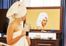 Woman with towel looking at the mirror Royalty Free Stock Photo