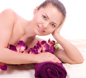 Woman with towel and pink orchid Stock Photo