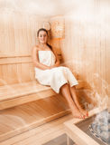 Woman in towel relaxing on bench at steamed sauna Royalty Free Stock Photography
