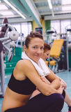 Woman with towel resting in the gym after training Royalty Free Stock Photo