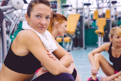 Woman with towel resting in the gym after training Royalty Free Stock Images