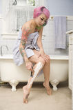 Woman in towel shaving her leg on side of the bathtub Stock Image