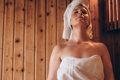 Woman sitting in a wooden spa with eyes closed. Woman in towel sitting in bathroom with eyes closed. Woman relaxing in a wooden enclosure during bath royalty free stock image