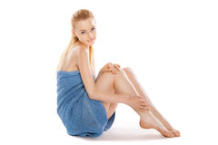 Woman in towel sitting on floor, stroking her legs Royalty Free Stock Images