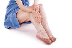 Woman in towel sitting on floor, stroking her legs Stock Photos