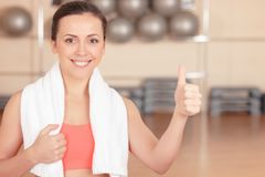 Woman with towel thumbing up in gym Stock Photography