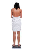 Woman in towel weighing herself Royalty Free Stock Images
