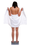 Woman in towel weighing herself Stock Photo