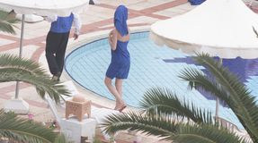 Woman in the towels walking close to swimming-pool stock images