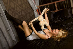 Woman with toy on black silk Royalty Free Stock Image