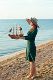 Woman with a toy ship Stock Image
