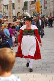 Woman in tpyical bavarian dress walks past people Royalty Free Stock Photo