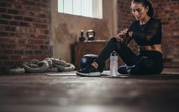 Woman tracking fitness progress on smart phone. Fit young woman sitting on a floor and looking at her smartwatch at fitness studio. Athlete looking at her royalty free stock photos