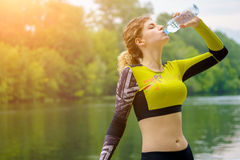 Woman in tracksuit drinking water in park Stock Photography
