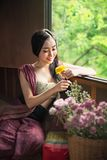 Woman in traditional asian dresses. Beautiful woman in traditional asian dresses holding flowers sitting near the windows stock photography