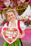 Woman in traditional Bavarian clothes or dirndl on festival. Young woman in traditional Bavarian clothes - dirndl or tracht -with a gingerbread souvenir heart on Stock Image