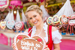 Woman in traditional Bavarian  dirndl on festival. Young woman in traditional Bavarian clothes - dirndl or tracht -with a gingerbread souvenir heart on a Royalty Free Stock Photo