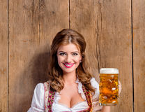 Woman in traditional bavarian dress holding beer Stock Photography