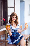 Woman in traditional bavarian dress holding beer and pretzel Royalty Free Stock Image