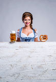 Woman in traditional bavarian dress holding beer and pretzel Royalty Free Stock Photography