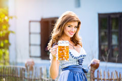 Woman in traditional bavarian dress holding mug of beer Stock Images