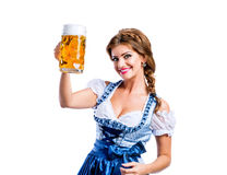Woman in traditional bavarian dress holding mug of beer Royalty Free Stock Images