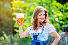 Woman in traditional bavarian dress holding mug of beer Stock Photography