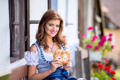 Woman in traditional bavarian dress holding pretzel, country hou Stock Images