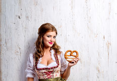 Woman in traditional bavarian dress holding pretzel, wooden back Stock Images