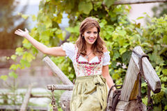Woman in traditional bavarian dress sitting on wooden horse Stock Images