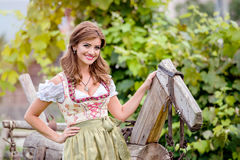 Woman in traditional bavarian dress sitting on wooden horse Stock Photography