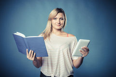 Woman with traditional book and e-book reader tablet royalty free stock image