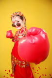 Woman in traditional Chinese costume and boxing gloves. Young Chinese woman in traditional red outfit with boxing gloves and sunglasses on yellow background Stock Image