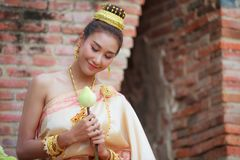 Woman in traditional clothes fold lotus flower petals used in rituals of Buddhism religion. A Lotus represents purity of body. Speech, and mind, floating above stock photos
